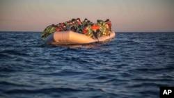 Des migrants et des réfugiés de différentes nationalités africaines attendent sur un bateau pneumatique surchargé au large des côtes libyennes, samedi 6 février 2021.
