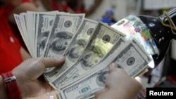 Nhân viên đếm đôla Mỹ bên trong một quầy đổi tiền ở Manila. Sự đóng góp của người Philippines ở nước ngoài đã chiếm gần 10% nền kinh tế Philippines trong năm vừa qua