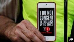 Seorang pria memegang iPhone-nya dalam sebuah demonstrasi mendukung privasi data di luar toko Apple di San Francisco (23/2). (AP/Eric Risberg)