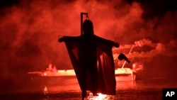 "People on a boat hold flares as they sail behind the effigy of Judas during the revival of the old Easter tradition of the ""burning of the Judas"", in the port town of Ermioni, in the Peloponnese peninsula, southwest of Athens, April 8, 2018."