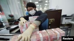 中國江蘇省南通市一家銀行的職員戴著口罩整理人民幣鈔票。(2020年1月30日)
