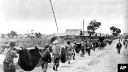 """美军1945年公布的从日方缴获的照片显示,在菲律宾被日军俘虏的盟军士兵抬着战友尸体。当年人们以为这反映的是""""巴丹死亡行军""""。2010年,美联社经调查判定这其实是一次盟军战俘葬礼并更正了图片说明。"""