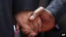 The hand of Chinese President Xi Jinping, left, holds the hand of Zimbabwean President Robert Mugabe, upon his arrival in Harare, Zimbabwe, Tuesday, Dec. 1. 2015