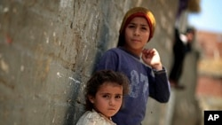 Two Palestinian refugee children lean on the wall of a house in Gezirat al-Fadel village, Sharqiya, about 150 kilometers (93 miles) east of Cairo, Egypt, May 17, 2013.