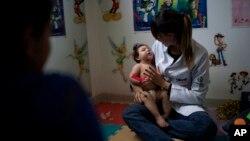 En esta foto del 27 de septiembre de 2016, Angélica Pereira, observa cómo su hija Luiza, de 1 año, discapacitada por el virus Zika, en una sesión de fisioterapia en el hospital UPAE de Caruaru, estado de Pernambuco, Brasil.