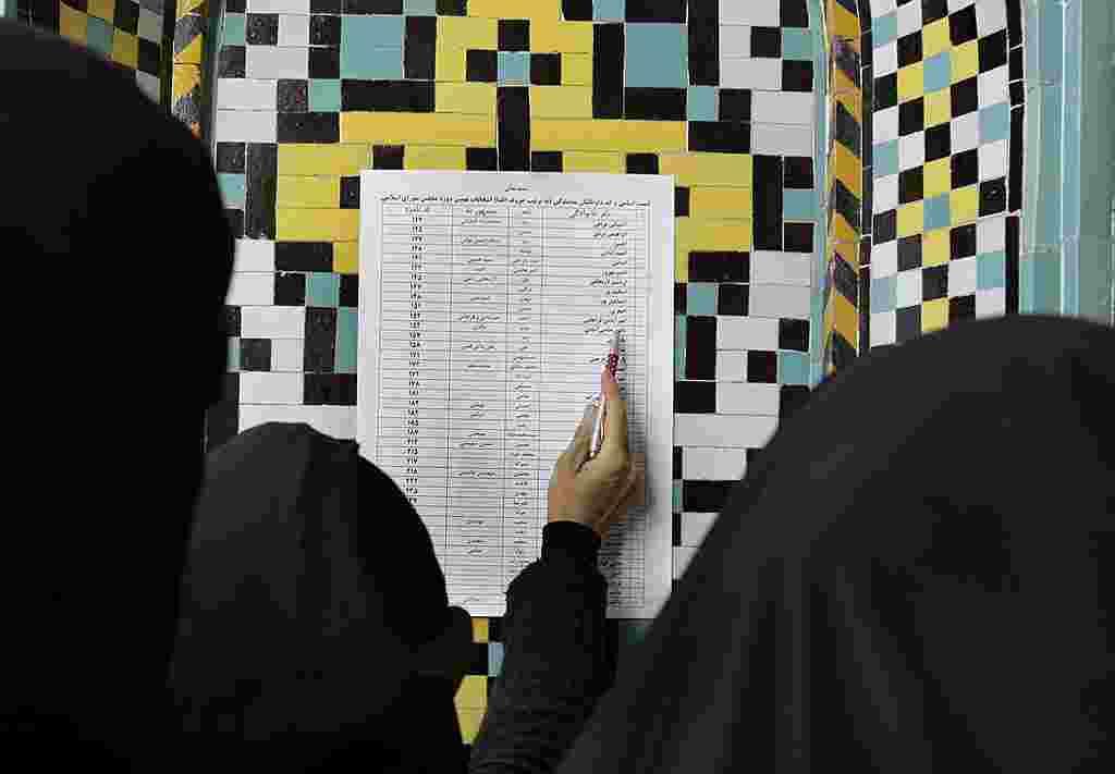 Una mujer iraní lee la lista de candidatos antes de votar en la mezquita de Masoumeh en ciudad Qom.