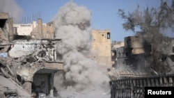Smoke rises after a landmine exploded as fighters of Syrian Democratic Forces are clearing roads after the liberation of Raqqa, Syria, Oct. 18, 2017.