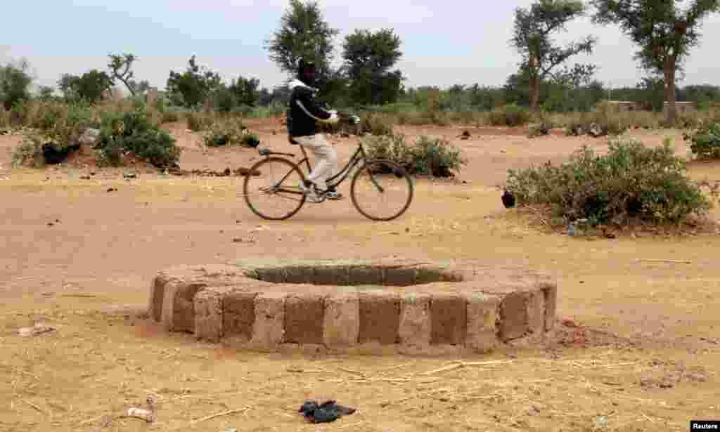 Un homme à vélo passe devant un puits de Sévaré où, selon Philippe Bolopion, directeur pour l'ONU de Human Rights Watch, des corps d'islamistes présumés auraient été jetés.