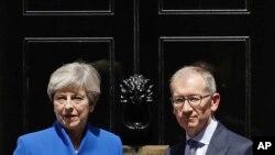 برطانوی وزیرِاعظم تھریسا مے اور ان کے شوہر وزیرِاعظم کی رہائش گاہ 10 ڈاؤننگ اسٹریٹ کے سامنے صحافیوں سے گفتگو کر رہے ہیں (فائل)