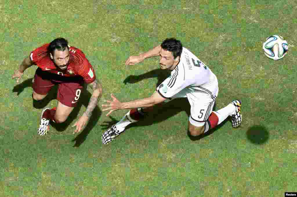 Portugal's Hugo Almeida fights for the ball with Germany's Mats Hummels during their 2014 World Cup Group G soccer match at the Fonte Nova arena in Salvador, June 16, 2014.