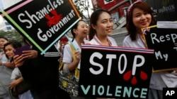 Para pekerja medis membawa poster memprotes pemerintah dalam demonstrasi di Bangkok (20/1). (AP/Wally Santana)