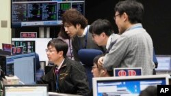 In this photo provided by the Japan Aerospace Exploration Agency (JAXA), staff of the Hayabusa2 Project watch monitors for a safety check at the control room of the JAXA Institute of Space and Astronautical Science in Sagamihara, near Tokyo, Feb. 21.