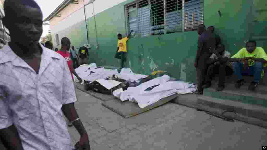 Un homme marche à coté des cadavres de vicitmes de l'accident survenu au festival de Port-au Prince lorsqu'un char au-dessus duquel des musiciens s'étaien tperchés a heurté un cable électrique haute tension, Haiti, le 17 février 2015.