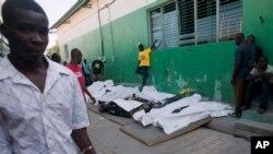 Des gens se promènent à coté des cadavres de victimes de l'électrocution lors du carnaval de Port-au-Prince, Haiti, le 17 février 2015.