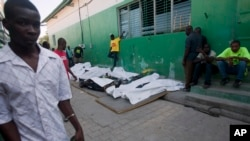 People walk past the bodies of victims who died during a carnival parade, lined up outside the morgue at the General Hospital in Port-au-Prince, Haiti, Feb. 17, 2015.