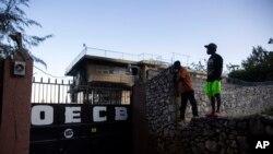 Warga berdiri di atas tembok untuk melihat ke dalam properti panti asuhan anak-anak yang dikelola oleh Church of Bible Understanding (COBU) yang terbakar bulan lalu di Kenscoff, pinggiran Port-au-Prince, Haiti, 14 Maret 2020. (Foto: dok).