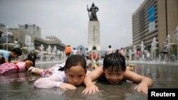Anak-anak bermain di air terjun di tengah udara musim panas di Gwanghwamun, Seoul, Juli 2014. (Reuters/Kim Hong-Ji)