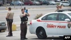 Polisi mengumpulkan barang bukti usai kerusuhan di kota Ferguson, Missouri, Senin (10/8).