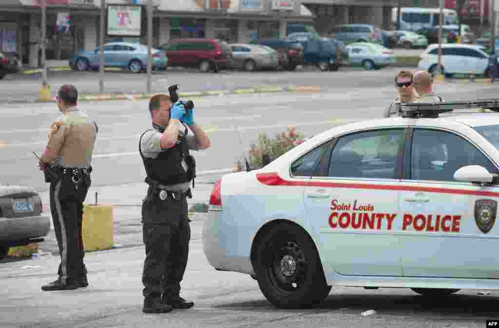 Polisi mengumpulkan bukti pada pagi hari setelah terjadinya penjarahan dan penembakan di sepanjang jalan West Flourissant di Ferguson, negara bagian Missouri (10/8), dalam demonstrasi yang menandai satu tahun ditembaknya remaja kulit hitam Michael Brown.