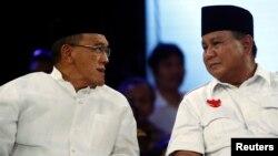 Ketua umum Partai Golkar Aburizal Bakrie dan kandidat presiden Prabowo Subianto dalam sebuah penampilan di televisi (9/7). (Reuters/Beawiharta)