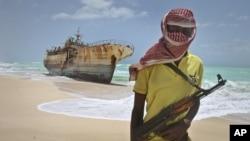 Một cướp biển Somalia bịt mặt đứng gần một thuyền đánh cá Đài Loan neo trên bờ sau khi những kẻ cướp biển được trả tiền chuộc và thả các thuyền viên, tại Hobyo, Somalia, nơi từng là hang ổ của cướp biển, 23/9/2012.
