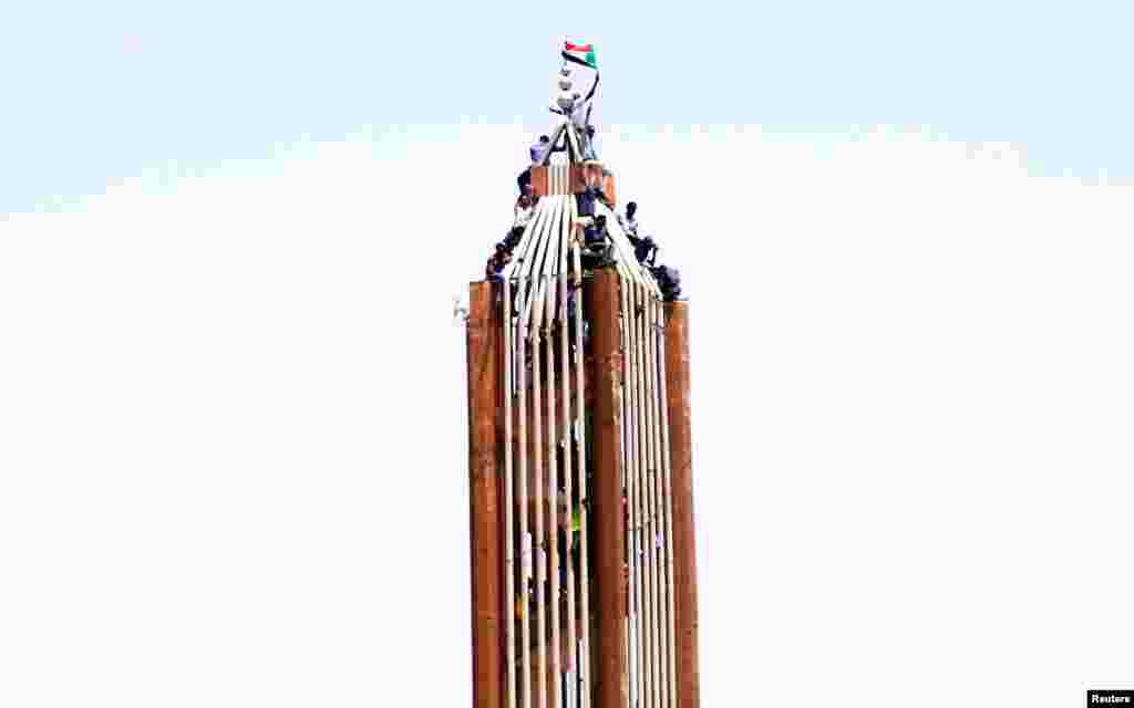 "Sudanese demonstrators hold their national flag on top of a building in Khartoum after the country's defense minister said that President Omar al-Bashir had been detained ""in a safe place"" and that a military council would temporarily run the country for two years."