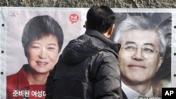 Một người dân dừng lại xem hình 2 ứng cử viên tổng thống Nam Triều Tiên Park Geun-hye (trái), và Moon Jae-in