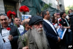 A demonstrator holds carnations during a protest to mark the anniversary of the nationwide summer 2013 Gezi Park protests, in Istanbul, May 31, 2017. Protests began in 2013 as a small environmental sit-in against government plans to raise a central Istanbul park and turned into nationwide demonstrations against the perceived authoritarian style of Turkey's then-prime minister and current president, Recep Tayyip Erdogan.