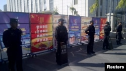 Policemen in riot gear guard at checkpoint on road near a courthouse where ethnic Uighur academic Ilham Tohti's trial is taking place in Urumqi, Xinjiang Uighur Autonomous Region, Sept. 17, 2014.