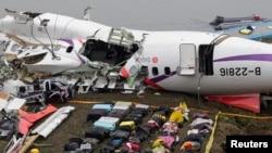 Tas-tas bags terlihat diletakkan di dekat reruntuhan pesawat TransAsia GE235 yang mengalami kecelakaan di kota New Taipei (5/2).