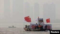 12月26日在湖北武汉,打着中国国旗、展示已故中共领导人毛泽东巨幅画像的船只引领着人们进行冬泳