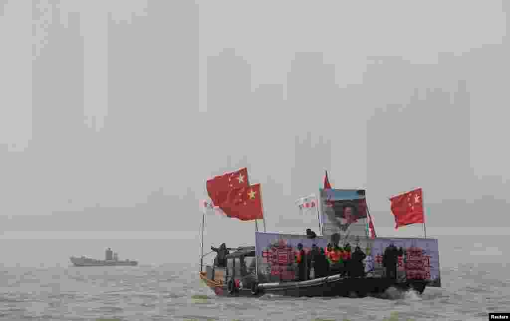 Boats carrying a giant image of Mao Zedong and Chinese national flags lead winter swimmers in the Yangtze River to celebrate the 120th birth anniversary of Mao in Wuhan, Hubei province, Dec. 26, 2013.
