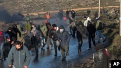 Para pemukim Yahudi berlarian dalam bentrokan dengan pasukan keamanan Israel yang mengevakuasi permukiman ilegal Amona di Tepi Barat, Rabu (1/2).