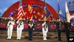 A military color guard prepares for the playing of the National Anthem at a 4th of July concert.