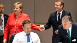 La canciller de Alemania, Angela Merkel, (izquierda) y el presidente de Francia, Emmanuel Macron, en el fondo, durante una desayuno de trabajo en la cumbre de la Unión Europea en Bruselas el viernes, 29 de junio de 2018.