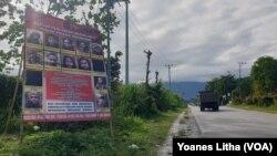 Baliho berisi Daftar Pencarian Orang (DPO) Kelompok Teroris Mujahidin Indonesia Timur (MIT) yang dipajang di sisi jalan Trans Sulawesi di Kecamatan Poso Pesisir, Poso. Jumat (11/12/2020). (Foto: VOA/Yoanes Litha)