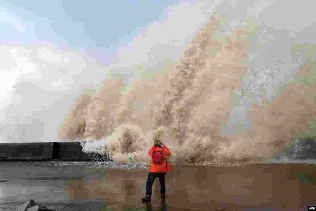 A woman takes photographs as waves crash over the tidal wall along the seafront in New Brighton, north west England.