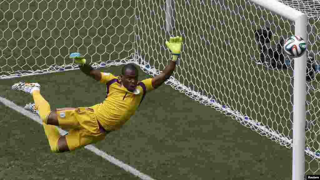 Nigeria's goalkeeper Vincent Enyeama jumps to make a save on a shot at goal by France's Paul Pogba.