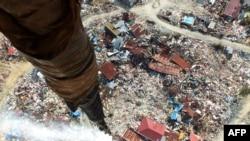 Disinfektan dilepaskan di suatu daerah di Palu yang terkena likuifaksi akibat gempa bumi 28 September dan di mana ribuan orang masih dikhawatirkan terkubur, 18 Oktober 2018. Aksi itu dilakukan untuk mensterilkan daerah terdampak.(Foto: AFP)