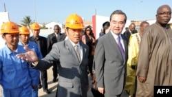 """中国外交部长王毅(右二)在塞内加尔文化部长阿卜杜•阿西塞•姆巴耶(右一)的陪同下,参观中国投资的塞内加尔""""黑人文明""""博物馆的建筑工地。"""