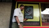 FILE - A man uses his mobile phone as he walks past a Zain customer care shop in Nairobi, Kenya, Feb. 15, 2010. Political activists in South Sudan have accused Zain South Sudan of disrupting their phone service ahead of a planned protest.