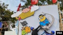 """香港社民連維園年宵攤位,諷刺新任警務處處長鄧炳強與中國國家主席習近平""""蛇鼠一鍋""""的巨型政治漫畫被食環署人員拆除。(美國之音 湯惠芸)"""
