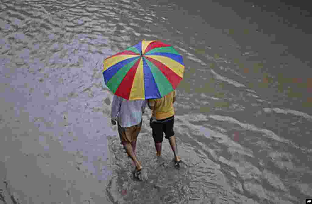 Men walk under an umbrella down a flooded street during a monsoon downpour in Lahore, Pakistan, September 16, 2011. (Reuters)