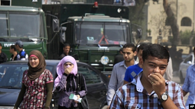 Egyptians cover their faces to avoid tear gas vapor as they walk at the site of clashes between protesters and anti-riot policemen near the Israeli Embassy in Cairo, Egypt, Sept. 10, 2011.