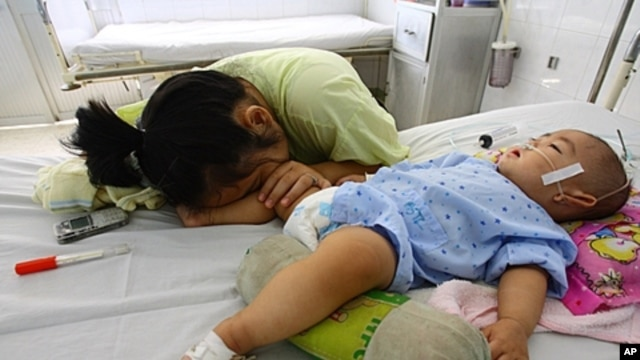 Nine-month-old boy Dao Xuan T, from the southern province of Binh Duong and affected by hand, foot and mouth disease, lies on a bed next to his sleeping mother at a local pediatric hospital in the southern province of Dong Nai, FILE August 24, 2011.