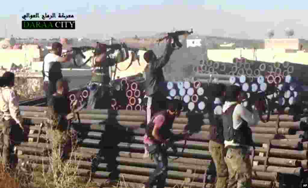 This image taken from video from the Sham News Network shows Syrian opposition fighters firing at government forces near Daraa, Sept. 25, 2013.