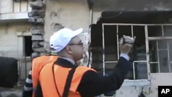In this image made from amateur video released by Shaam News Network purports to show Arab League monitors visiting the Baba Amr area of Homs in Syria, December 28, 2011. (AP cannot independently verify the content, date, location or authenticity of this