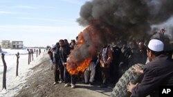 ຊາວອາຟການິສຖານ ພາກັນຈູດຕີນລົດປະທ້ວງຕໍ່ຕ້ານສະຫະລັດອາເມຣິກາ ທີ່ Muhammad Agha, ແຂວງ Logar ທາງໃຕ້ຂອງ Kabul, Afghanistan, ເດືອນກຸມພາ ທີ 25, 2012. ຍ້ອນວ່າມີການຈູດຄໍາພີ Quran ທີ່ຖານທັບ NATO.