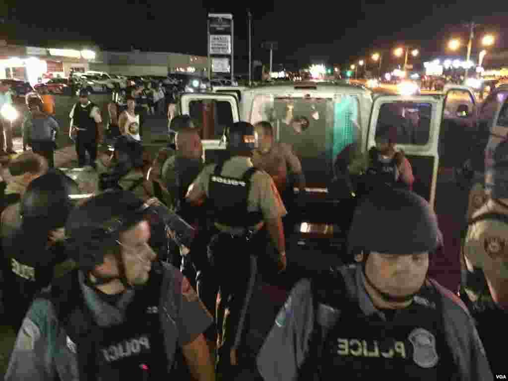 Polisi menahan tersangka pelaku kerusuhan di West Flourissant di Ferguson, negara bagian Missouri (10/8). (VOA/Kane Farabaugh)