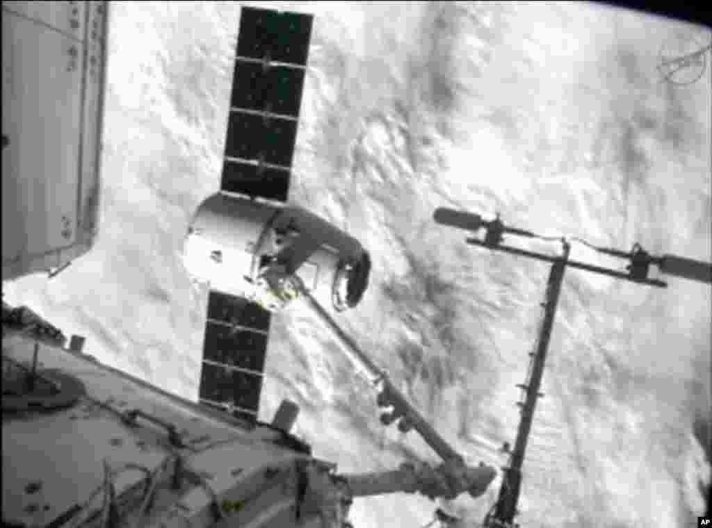 ພາບຈາກລາຍການໂທລະພາບຂອງອົງການ NASA-TV ສະແດງໃຫ້ເຫັນແຂນຂອງຫຸ່ນຍົນ ຫລື ໂຣບອັດຈັບຍານອະວະກາດ Dragon ຢູ່ສະຖານີຍານອາວະກາດສາກົນ ໃນຂະນະທີ່ພວກຍານດັ່ງກ່າວຜ່ານມະຫາສະມຸດ ອັດລັງຕິກໄປ ໃນວັນທີ 10 ຕຸລາ, 2012.
